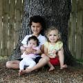 Maia and her brother and sister sitting against a tree with her brother holding her in his arms